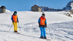 Blindenschneesport Unterricht, der Sehbehindert fährt voraus, der Skilehrer gibt Anweisungen und Tipps, ein eingespieltes Team