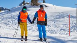 Skilehrer und Sehbehinderter Hand in Hand am Skifahren dank Spenden