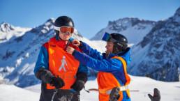 Schneesportlehrer bringt das Funkgerät an